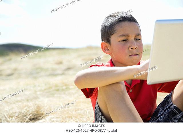 Little boy using digital tablet on field