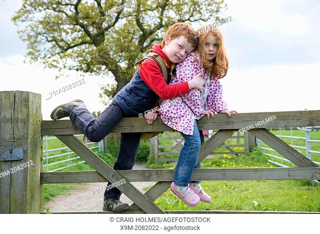 Brother and sister on a gate in the countryside
