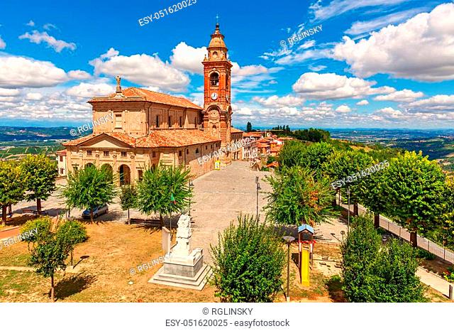 Parish church on town square under beautiful blue sky with white clouds surrounded by green trees in small town of Diano d'Alba in Piedmont, Northern Italy