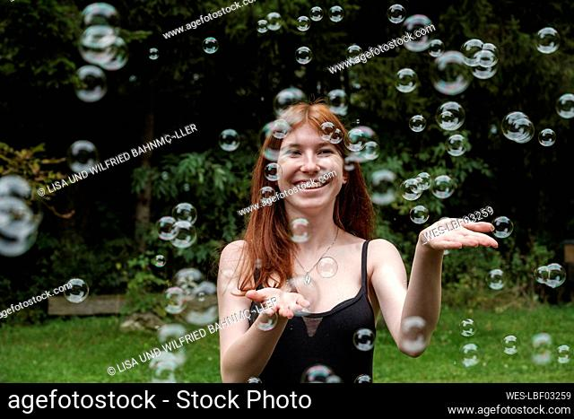 Happy woman playing with soap bubbles in yard