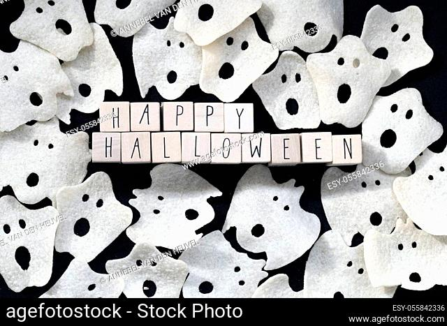 Words Happy Halloween with various ghost on black background top view, scary ghost horror concept closeup