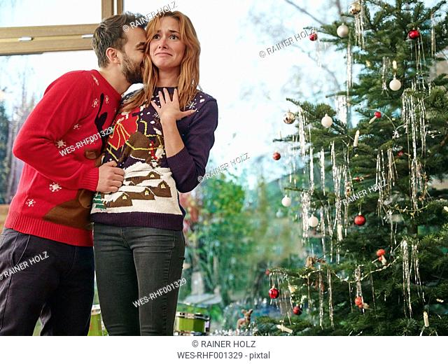 Couple standing in front of Christmas tree, man kissing surprised woman