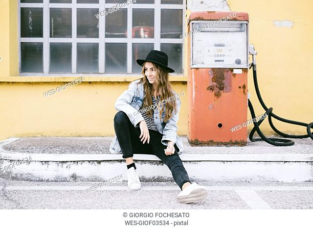 Fashionable young woman wearing hat sitting beside an old petrol pump