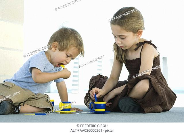 Brother and sister sitting on the ground, playing with plastic teacups together