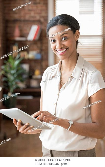 Mixed race businesswoman using digital tablet in office