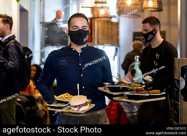 Illustration a waiter wearing a mask bringing plates to the table at the restaurant Poule et Poulette in Brussels, Monday 08 June 2020