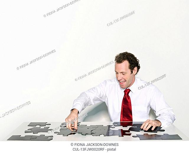 A business man doing a jigsaw