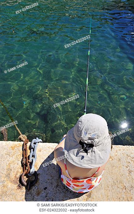 Girl (9) fishing on wharf, Marseille, France