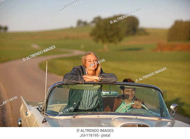 Couple Driving On Country Road In Open Top Classic Car