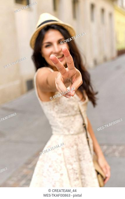 Happy young woman doing victory sign