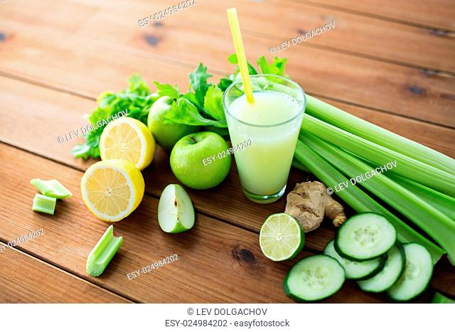 healthy eating, food, dieting and vegetarian concept - close up of glass with green juice, fruits and vegetables on wooden table