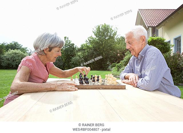 Senior couple playing chess in garden