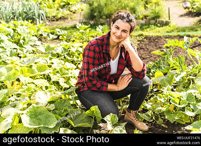 Young woman with hand on chin kneeling amidst vegetables growing in garden