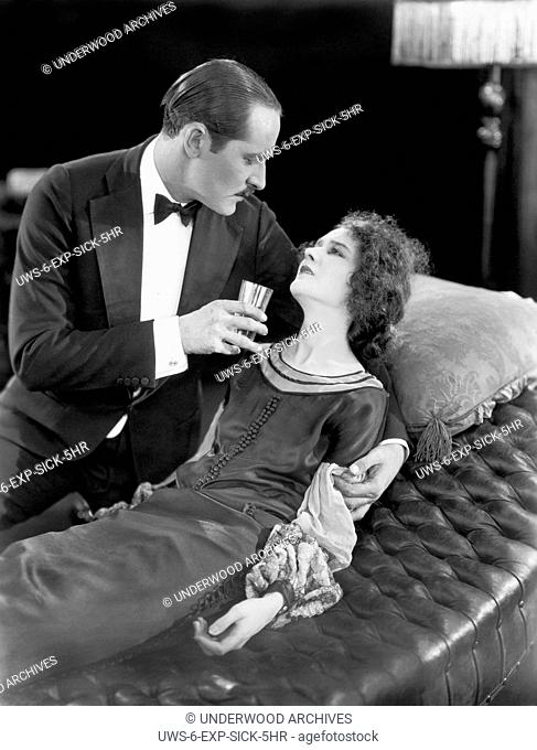 Hollywood, California: 1925 A scene in the early silent movie, Fifth Avenue Models, with actor Norman Kerry tending to an ill Mary Philbin