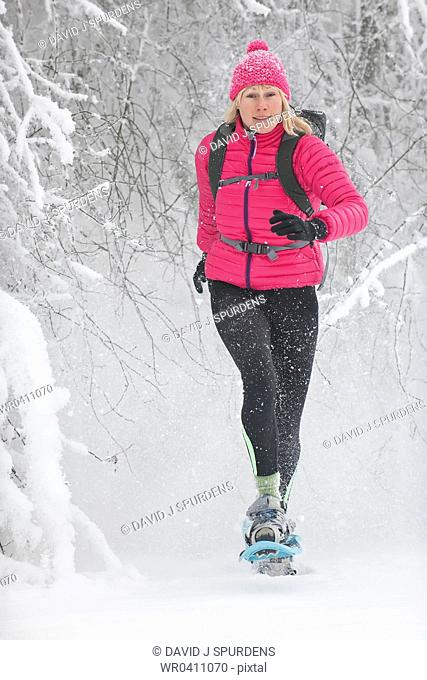 A woman snowshoeing running through a snowy trees