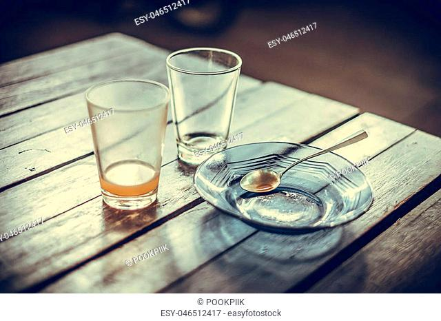 Empty glass of hot tea in with saucer and spoon on wooden table in the morning vintage tone, shallow focus