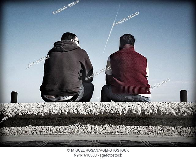 Two young men sitting drinking beer paths