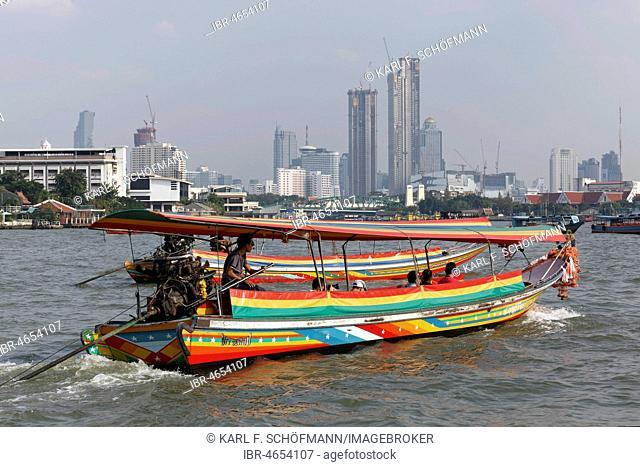 Longtail boat on the Mae Nam Chao Phraya River, skyline financial district Bang Rak, Bangkok, Thailand