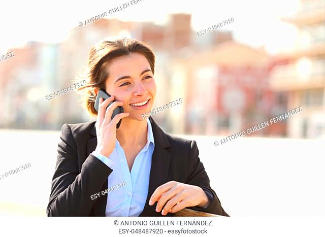 Happy businesswoman talking on phone sitting on a bench in a park