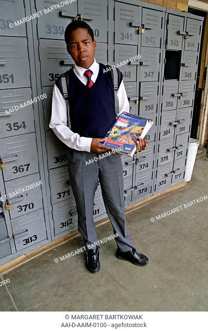 School boy by lockers, St Mark's School, Mbabane, Hhohho, Kingdom of Swaziland