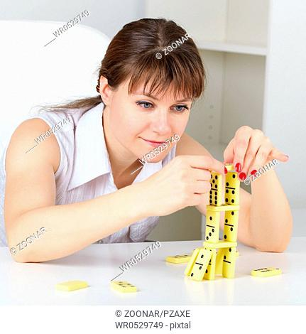 Funny woman are concentrated in building a tower with domino