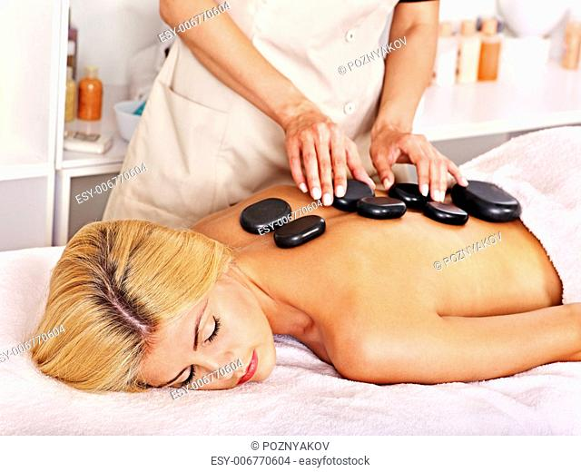 Satisfied blond woman getting massage in spa