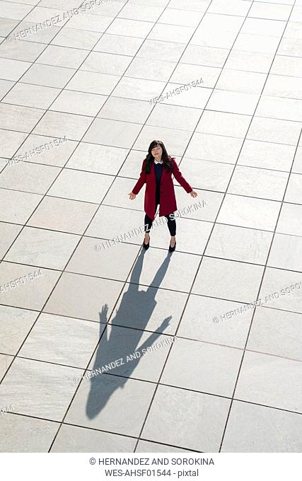 View from above of walking modern businesswoman standing on concrete floor with arms open
