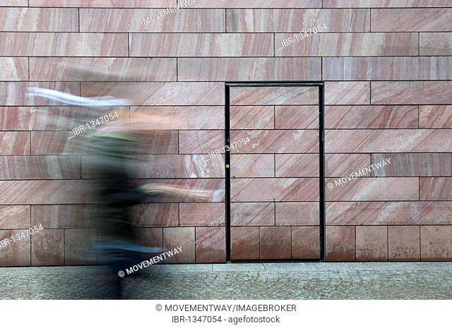 Hurried person in front of a neutral wall
