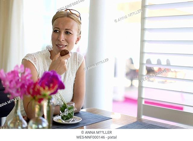 Portrait of blond woman with chocolate cookie and glass of peppermint tea