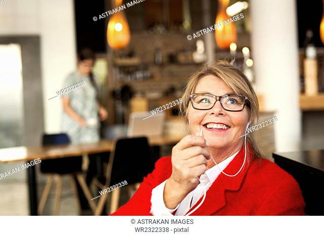 Happy businesswoman talking through earphones at restaurant
