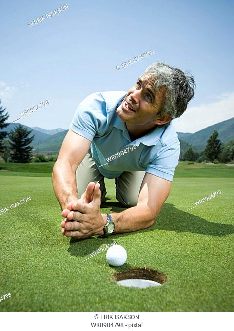 Close-up of a man kneeling in front of a golf ball near a hole and praying