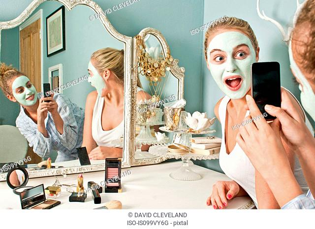 Woman wearing face mask being photographed by friend