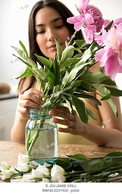 Hispanic woman arranging pink flowers in jar