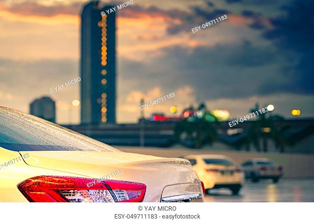 Rear view of car parked in the city near high building after rain with grey and orange sky and clouds and have water droplet on surface of car