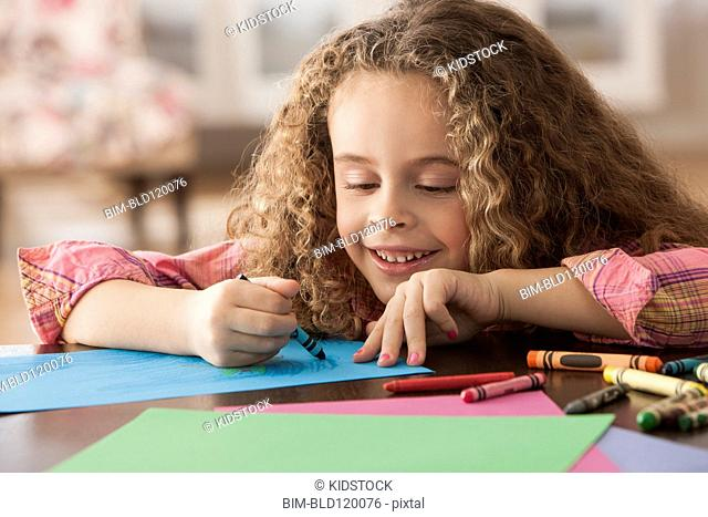 Hispanic girl drawing at table