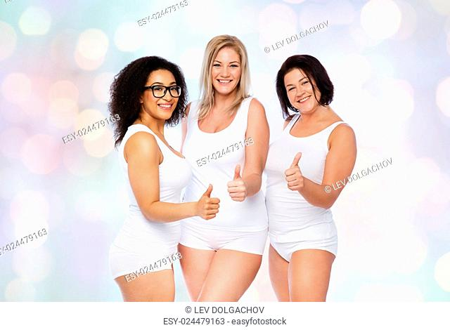 gesture, friendship, beauty, body positive and people concept - group of happy plus size women in white underwear showing thumbs up over holidays lights...