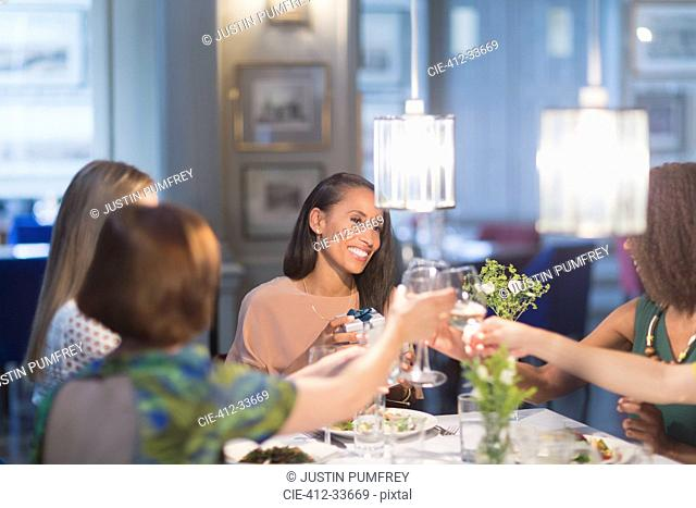 Smiling women friends toasting white wine glasses dining at restaurant table