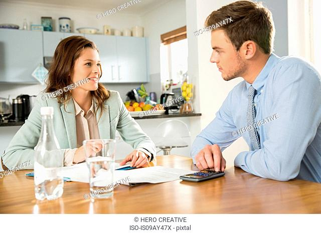 Young couple at kitchen table discussing and calculating bills