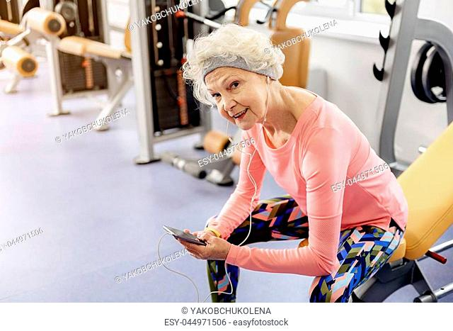 Portrait of beaming grandmother hearing song. She sitting on bench in fitness center