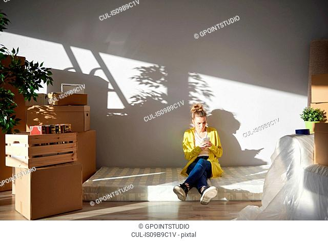 Young woman sitting on mattress in new home, using smartphone