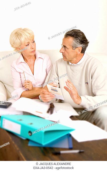 Senior couple paying bills on sofa