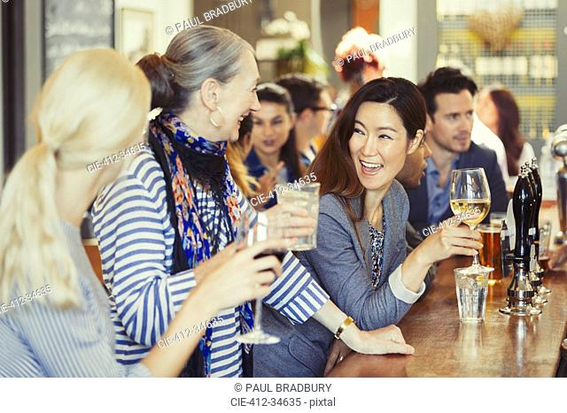 Smiling women friends drinking wine at bar