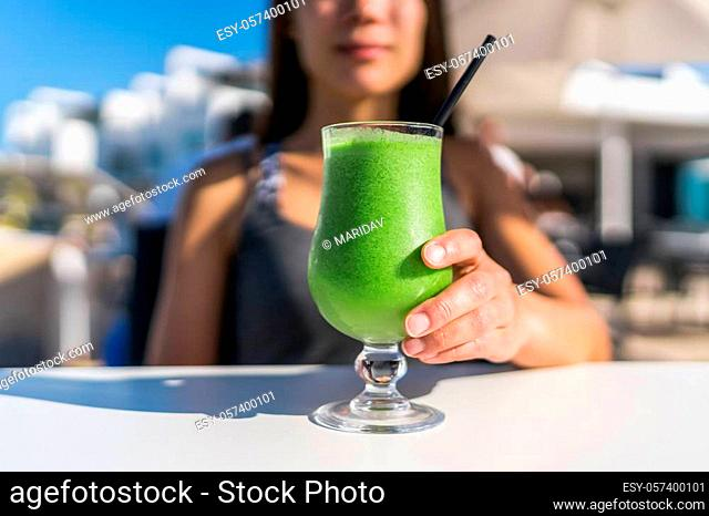 Healthy juicing lifestyle trend woman drinking green spinach juice smoothie cup at restaurant table. Unrecognizable person holding glass of fresh vegetables...