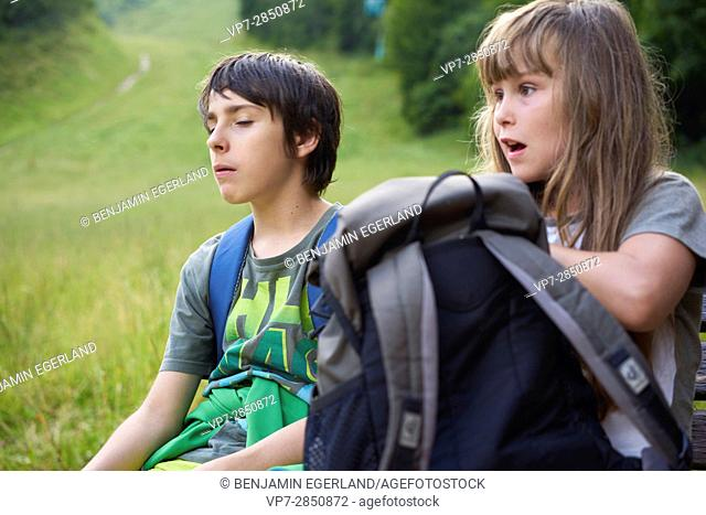 two siblings sitting on bench in nature
