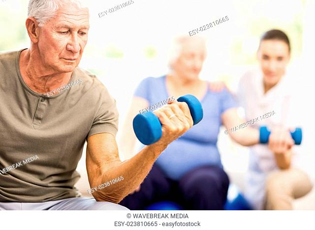 Physiotherapist helping patients with exercises