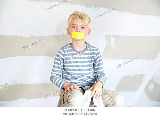Portrait of boy with taped mouth sitting on ladder in attic to be renovated