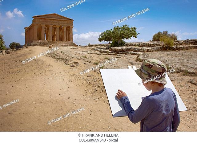Boy drawing in sketchpad in front of the Temple of Concordia, Agrigento, Sicily, Italy
