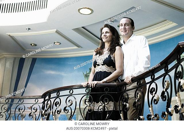 Low angle view of a mid adult couple standing at the balcony of a ship and smiling