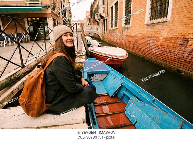 Woman sitting by canal, Venice, Italy