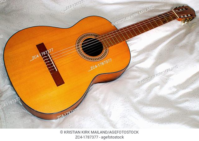 Classic wooden guitar on bed sheet